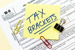 A W9 tax form with Tax Brackets written on a yellow sticky note.